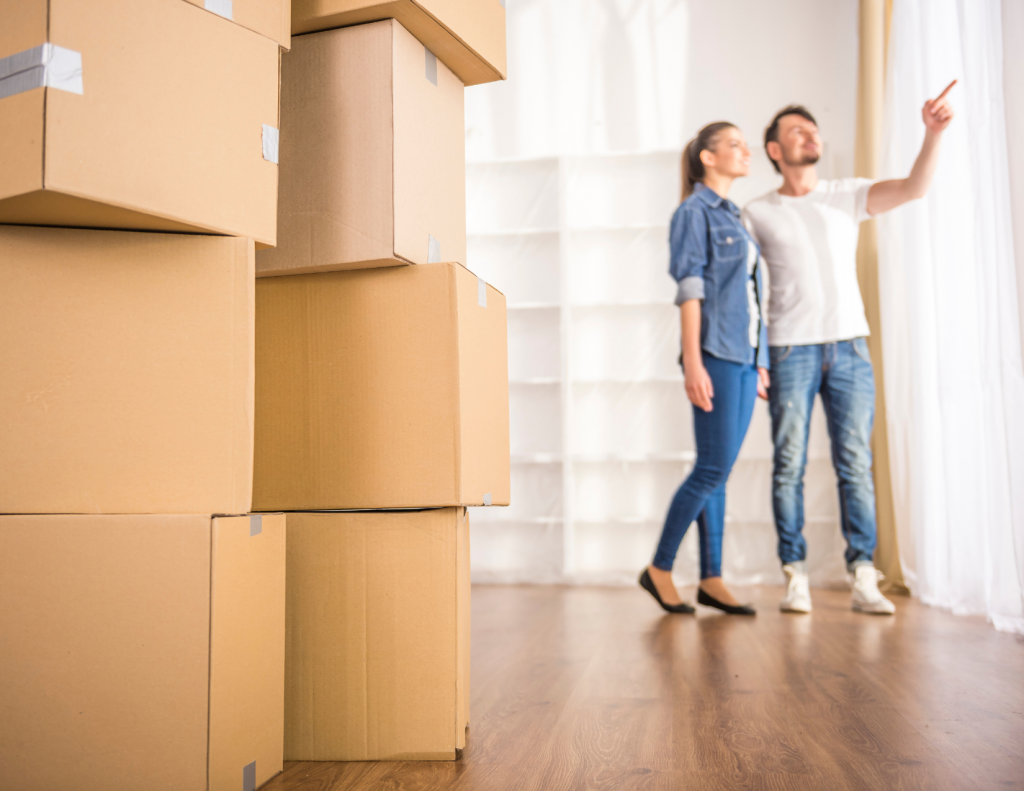 A couple with moving boxes inside a house