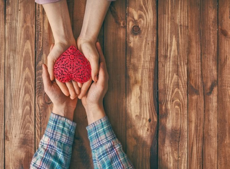 Hands of man and woman holding red heart on wooden background. Concept of Valentine's Day. Top view. Close up.