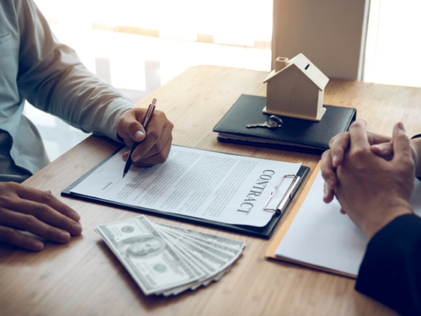 New home buyers are signing a home purchase contract at the agent's desk.