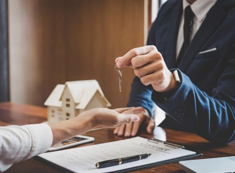 Real estate agent Sales manager holding filing keys to customer after signing rental lease contract of sale purchase agreement, concerning mortgage loan offer for and house insurance.