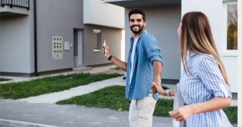 Couple holding hands with a key about to enter their new home
