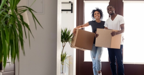 Couple holding boxes inside a house